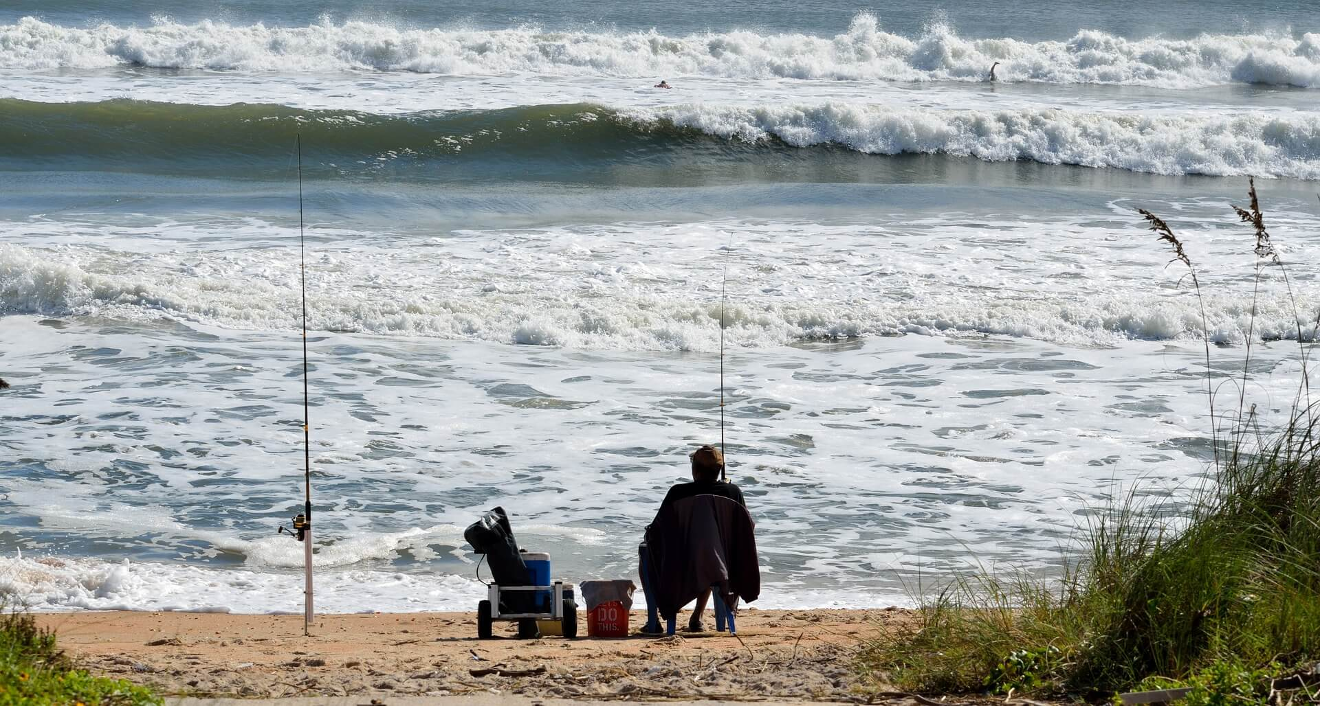 fisherman surf fishing in the beach
