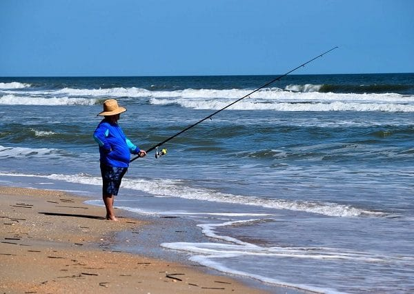 Fishing intusiast is surf fishing in the beach